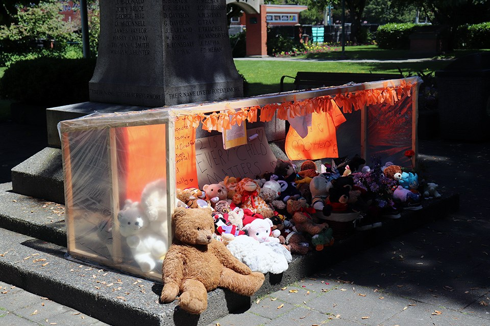 A vigil in Port Coquitlam's Veteran Park honours the 215 children found in unmarked graves at a former Kamloops residential school with teddy bears, stuffed animals, shoes and notes from local residents.