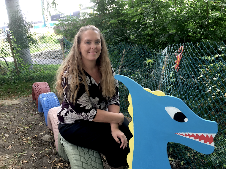 Port Moody Station Museum manager Brianne Egeto takes a seat on a colourful dragon in the new enchanted garden.