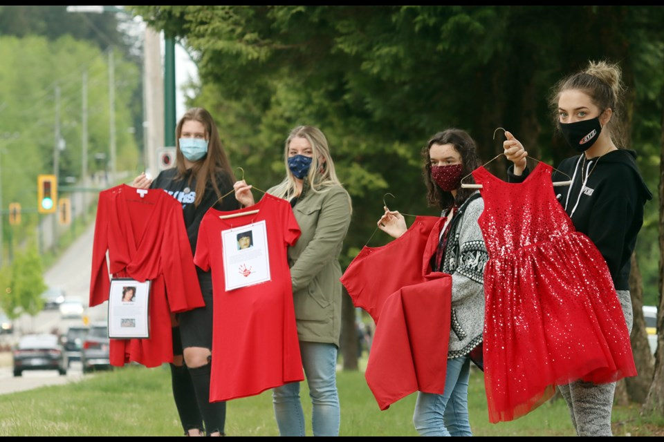 Grade 12 Social Justice students Jamie Livgard, Ellisa White and Ciara Albrecht, along with their teacher, Megan Leslie, prepare to hang red dresses to commemorate missing and murdered Indigenous women in front of Dr. Charles Best secondary school.