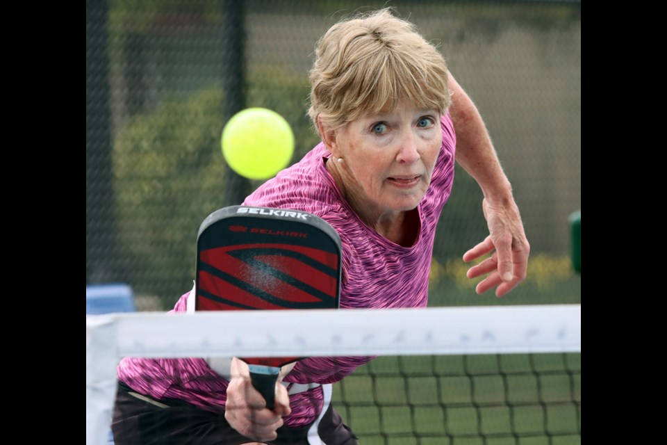 Brenda Martel returns a volley during a pickleball match at the courts near Dogwood Pavillion in Coquitlam on Friday.
