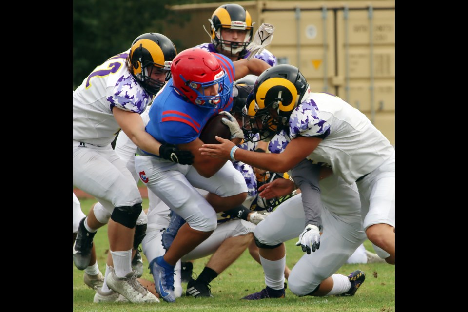 MARIO BARTEL/THE TRI-CITY NEWSCentennial Centaurs running back Ziad Sabry is swarmed by Mt.Douglas Rams tacklers in the first quarter of theri BC High School Football varsity exhibition game, Friday at Centennial. Mt. Douglas won the game, 19-13. It was the first competitive game in almost two years for both sides because of COVID-19 public health restrictions that limited players to practising.