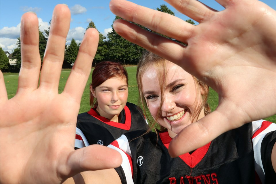 Kali McCready (right) and Robin Rothwell are each taking on a new challenge as the seniors are playing wide receiver for the Terry Fox Ravens. Neither has played football before.