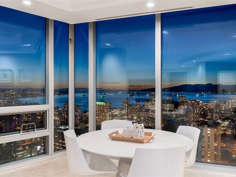 Table with a view set up in a corner space of this luxury 'sky home' with floor-to-ceiling windows custom-designed for a 'Hollywood action star' in downtown Vancouver. The unit is listed for just under $13 million.