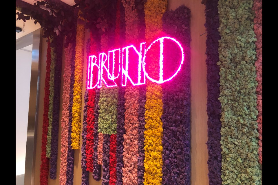 Bruno's neon sign is on a wall designed for people to pose for pics in front of
