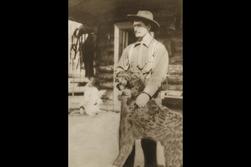 John G. Lind in front of cabin with a dog. [after 1896]