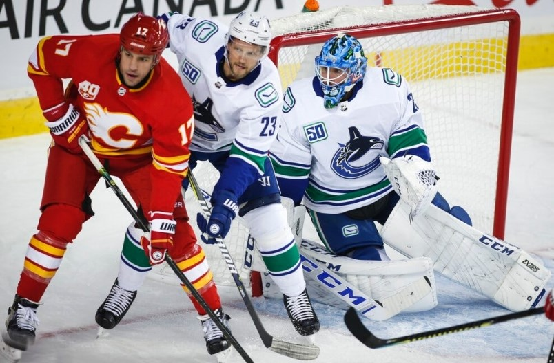 milan-lucic-and-alex-edler-battle-for-position-in-front-of-jacob-markstrom