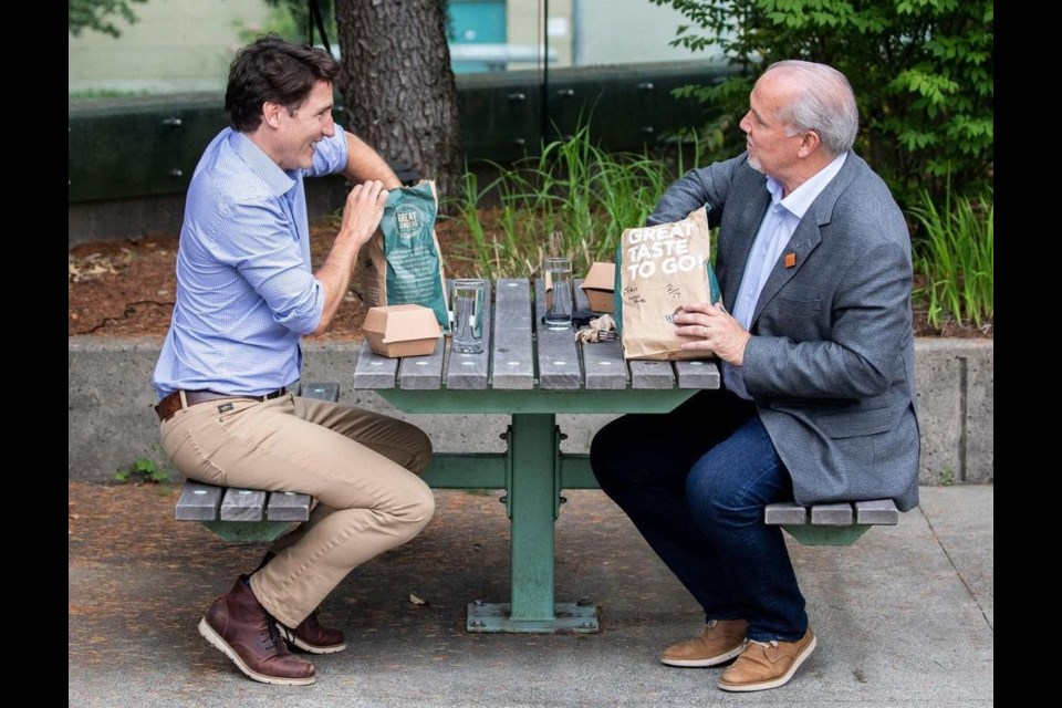 Prime Minister Justin Trudeau, left, and B.C. Premier John Horgan sit down at a picnic table with take-out food from the White Spot in Coquitlam.