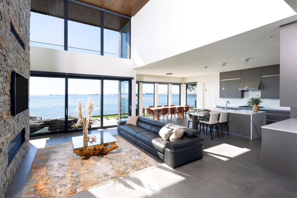 The addition of a four-storey fully enclosed elevator connects the beach level home to the hillside garage in this stunning west coast modern Tsawwassen new custom home.