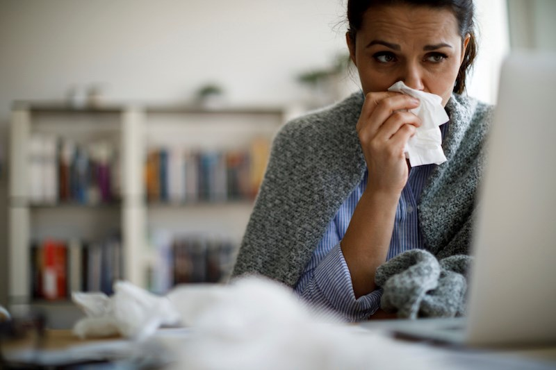 woman-blowing-nose-sick-influenza-virus