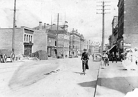 1900 - A woman rides a bicycles south along Granville Street.
