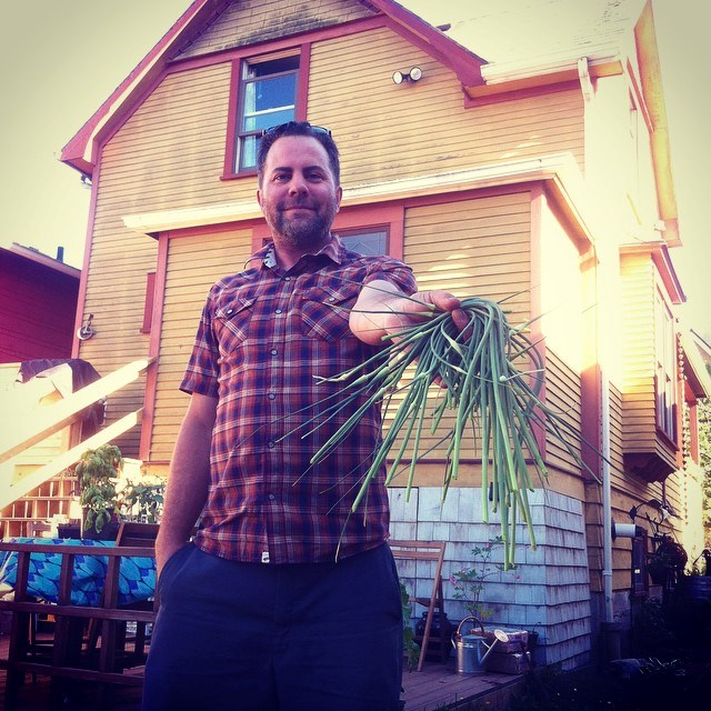 Geoff Huffman with homegrown goods in the backyard of Katy and Geoff Huffmans' heritage house in Hastings Sunrise. They have been planting trees and landscaping inspired by old photos of what was once on the site. They managed to get some grapevine cuttings in the neighbourhood to revive grape growing  that once took place. Photo credit: Huffmans.