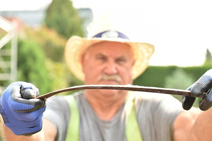 Roofer David Hodgson shows the flexibility of a boiled shingle. Photo Dan Toulgoet