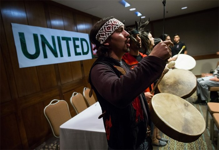 Swo Wo Gabriel, of the Squamish First Nation, sings and plays a drum before First Nations and environmental groups speak about a federal court hearing about the Kinder Morgan Trans Mountain pipeline expansion, during a news conference in Vancouver, B.C., on Monday October 2, 2017. The hearing which began Monday consolidates numerous lawsuits filed by seven First Nations applicants, the cities of Burnaby and Vancouver, the Raincoast Conservation Foundation, and the Living Oceans Society, which claim the National Energy BoardÕs approval process was flawed and First Nations werenÕt adequately consulted. THE CANADIAN PRESS/Darryl Dyck