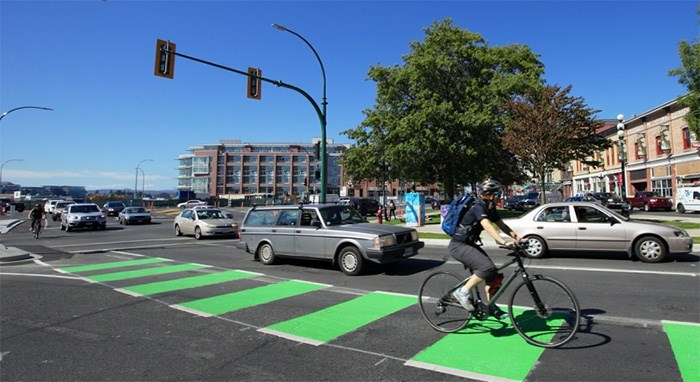 A cyclist rides in a bike lane along Johnson Street in Victoria, well separated from vehicles.