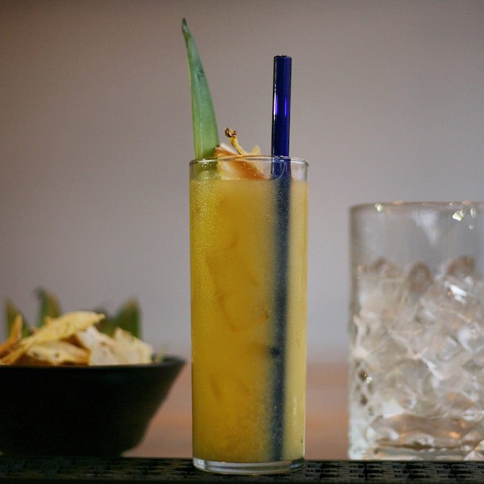 A cocktail from The Cascade Room served with a glass straw (
