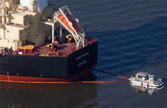 A spill response boat secures a boom around the bulk carrier cargo ship MV Marathassa after a bunker fuel spill on Burrard Inlet in Vancouver, B.C., on April 9, 2015. A trial for a vessel and a company that were charged after thousands of litres of bunker fuel spilled off British Columbia's coast nearly three years ago began in provincial court today without one defendant attending the court hearing. THE CANADIAN PRESS/Darryl Dyck