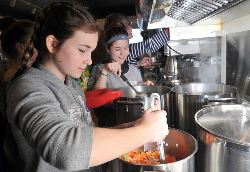 MARIO BARTEL/THE TRI-CITY NEWS Ana Iancu and Chelsea Wilson, students from Pitt River middle school, carmelize the vegetables for the soup they're making at Gallery Bistro that will be donated to a women's shelter in the Tri-Cities.