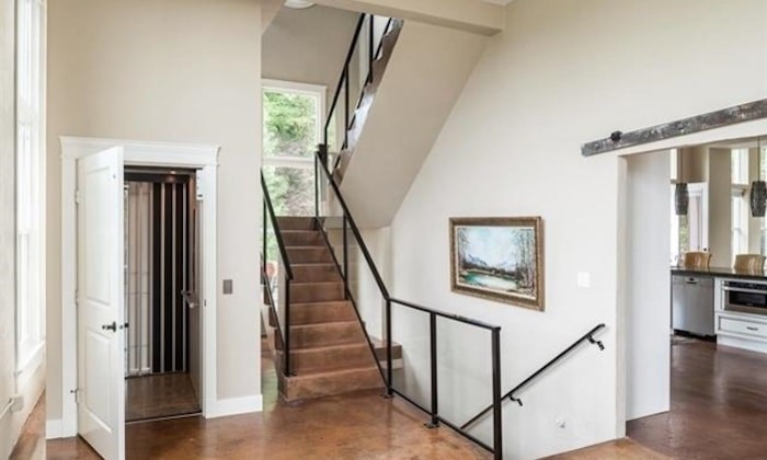 You can see the concrete floors, the elevator installed in place of a previous shaft, the stairs--including a post at the landing that is adapted from the original (Photo via RE/MAX All Points Realty)