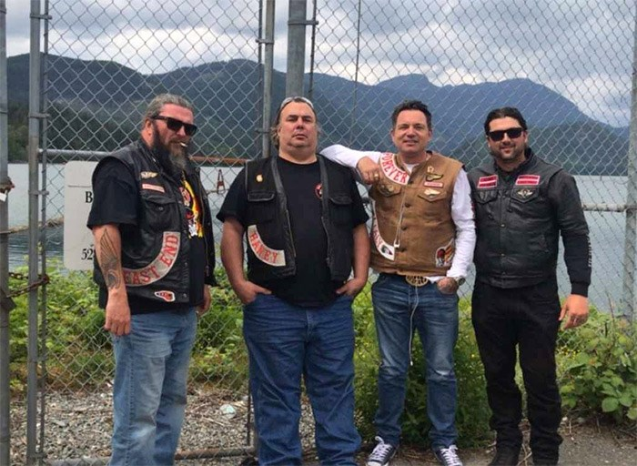 Burnaby firefighter Nick Elmes, right, poses with members of the Hells Angels Motorcycle Club.