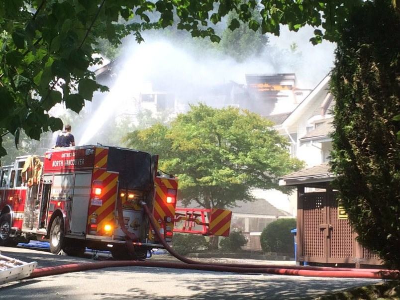 District of North Vancouver firefighters battle a blaze at Lions Manor Deep Cove, a seniors complex in Deep Cove Tuesday afternoon. Fire crews were still fighting the fire at press time. About 100 people had been evacuated to Parkgate Community Centre. photo Paul McGrath, North Shore News