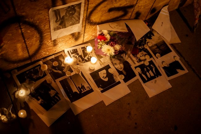 Pictures of Danforth shooting victim Reese Fallon, are left with candles at a makeshift memorial remembering the victims of a shooting on Sunday evening on Danforth, Ave. in Toronto on Monday, July 23, 2018. THE CANADIAN PRESS/Mark Blinch