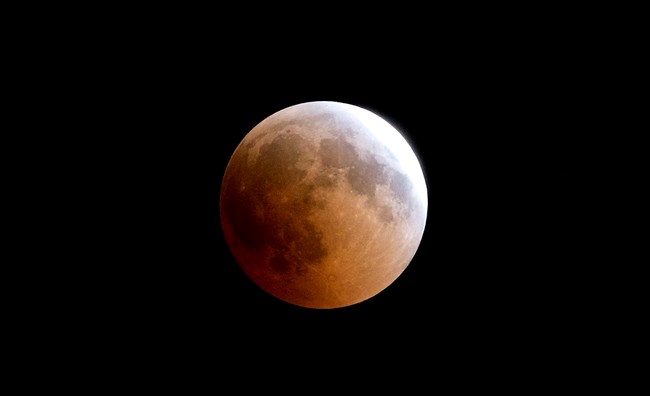 A blood moon rises over Gaza City, Friday, July 27, 2018. Skywatchers around much of the world are looking forward to a complete lunar eclipse that will be the longest this century. The so-called