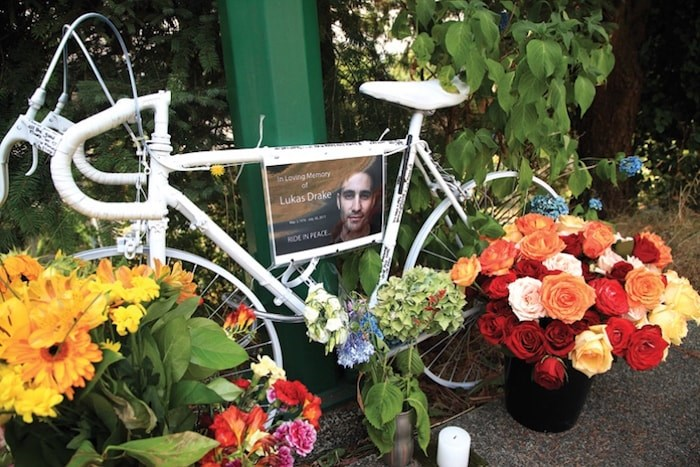 """Floral tributes surround a """"ghost bike"""" memorial on Shavington Street for a cyclist killed in a nearby collision, in this image taken days after the July 2017 crash. file photo Kevin Hill, North Shore News"""
