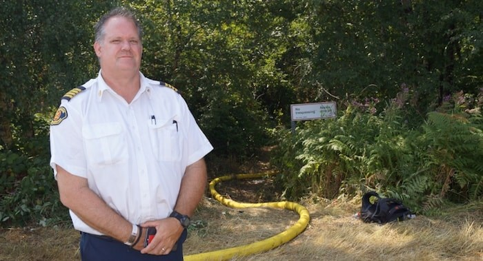 Richmond Fire Rescue Deputy Chief Kevin Gray stands at the entrance of a trail to the DND lands fire. After a week of battling the 12-hectare blaze, crews are trying to saturate the ground to extinguish an underground bog fire. (Richmond News)