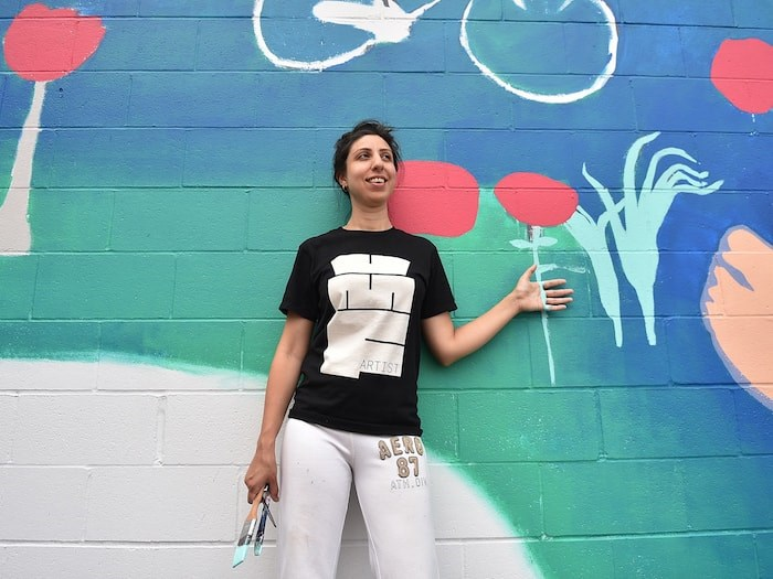 Painter Sara Khan stands in front of her mural in progress for this year's Vancouver Mural Festival, which runs Aug. 6 to 11. Photo Dan Toulgoet