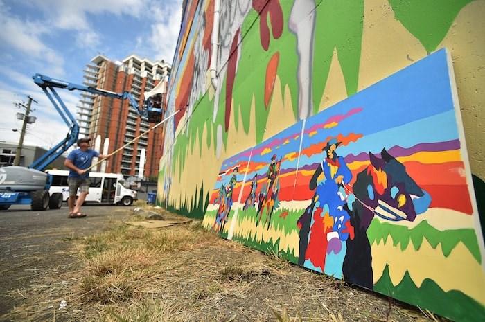 Artist Jean Paul Langlois and volunteer Bryce Ferris work on