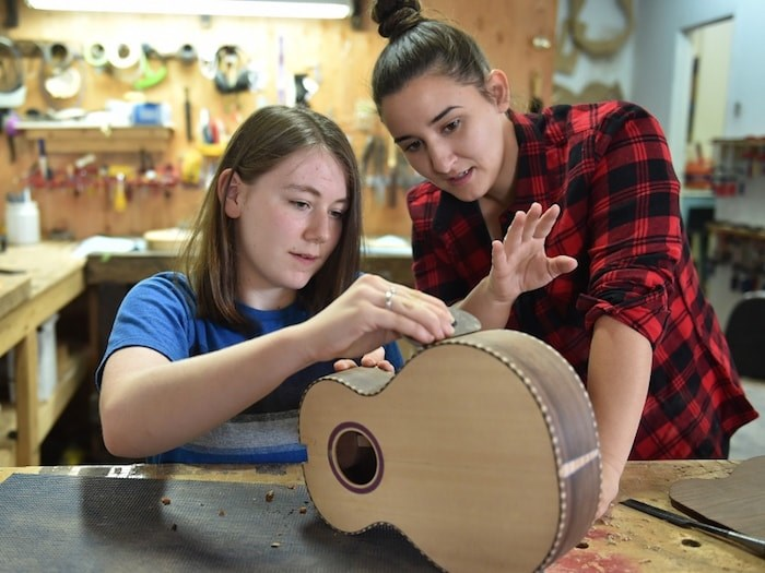 Vancouver luthier and festival co-founder Meredith Coloma shows her 14-year-old student Caitlin McCracken the nuances of guitar building.