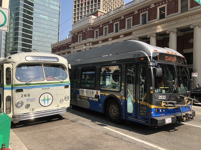 The vintage trolleybus next to an operating TransLink trolleybus in front of Waterfront Station (Lindsay William-Ross/Vancouver Is Awesome)