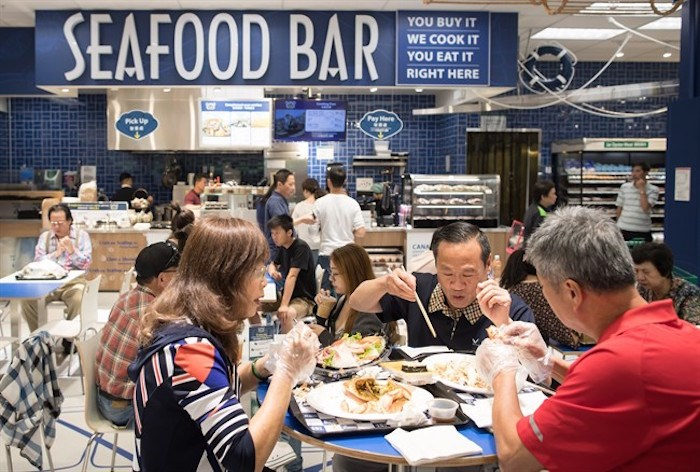 People eat at a seafood bar at T&T Supermarket's newest location, in Richmond, B.C., on Tuesday August 21, 2018. Shoppers can purchase fresh seafood in the store and have it steamed or baked to be eaten on site. Grocery stores increasingly blur the line between supermarkets and restaurants with large chains adding take-out meals to their shelves, hot food counters where chefs make dishes to order and even full-service restaurants. Dubbed grocerants, these combination spaces serve a time-strapped population that values convenience. THE CANADIAN PRESS/Darryl Dyck