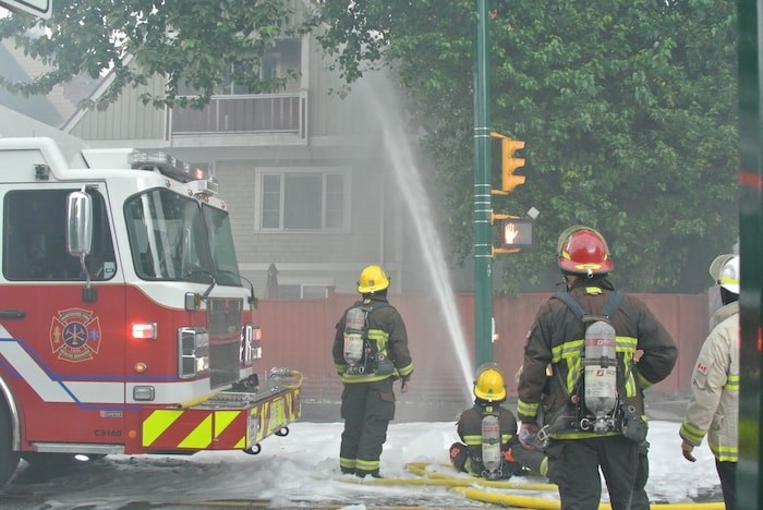 Vancouver firefighters douse the house at Macdonald and West Third on August 23. - Martha Perkins