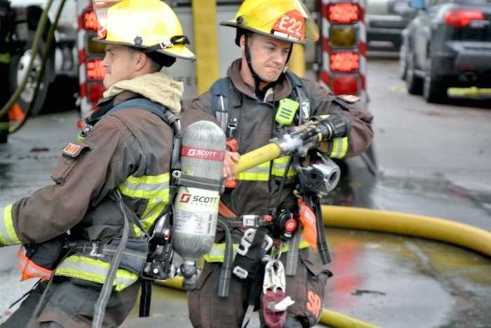 Vancouver firefighters drag the hose to the other side of Macdonald and West Third. - Martha Perkins