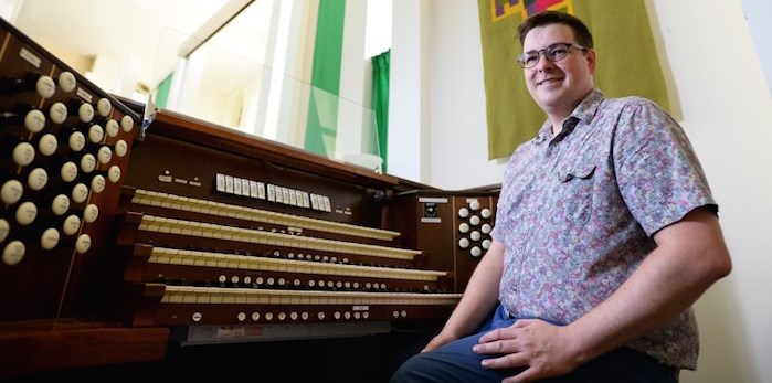 Holy Trinity Anglican Church's musical director Michael Park along with the church's 106-year-old Casavant organ.