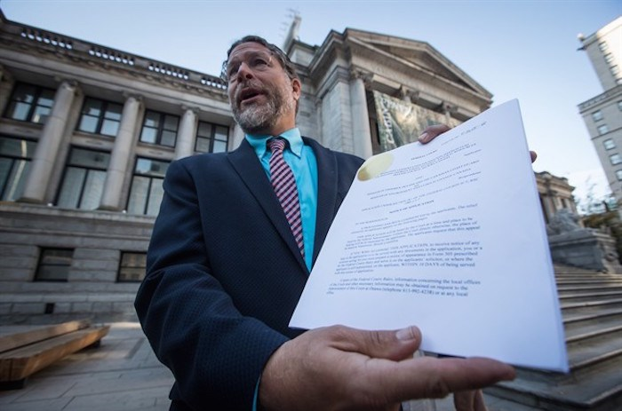 Jay Ritchlin, David Suzuki Foundation Director-General for Western Canada, holds a copy of a lawsuit conservation groups filed in federal court against Fisheries and Oceans Canada regarding the protection of southern resident killer whales, during a news conference in Vancouver, on Wednesday September 5, 2018. THE CANADIAN PRESS/Darryl Dyck