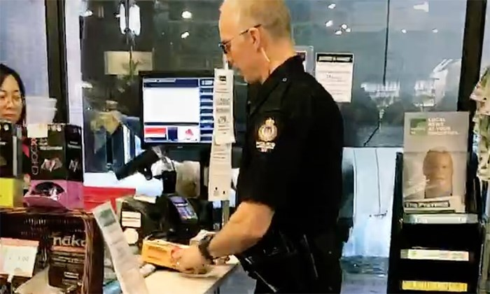A video shows what appears to be stolen cheese being returned to a store by a VPD officer. Kurtis Kolt/Screengrab