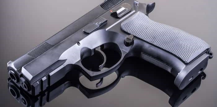Photo: hand gun on glass table / shutterstock