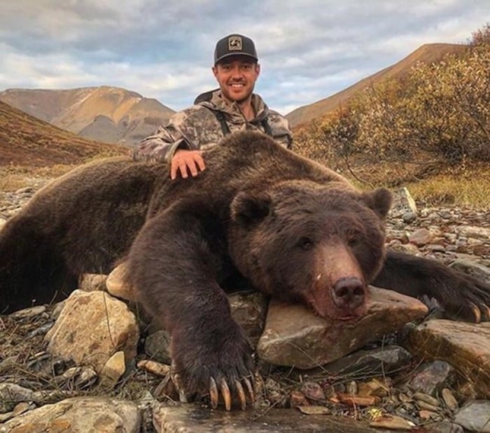 Tim Brent poses with a grizzly bear in this photo from his Twitter page @Brenter37. A former professional hockey player is facing a backlash on social media after he posted photos of a massive grizzly bear he hunted in Yukon. Tim Brent, who was born in Ontario and played for several teams in the NHL, posted the photos on Facebook and Twitter on Sept. 10.(THE CANADIAN PRESS/HO, Twitter, @Brenter37)