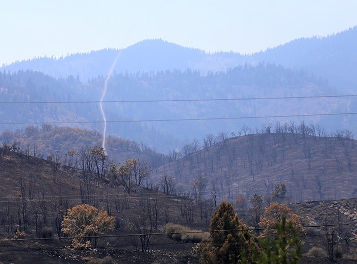 A small tornado whips around a burned out hillside in the northernmost part of California. Photo Bob Kronbauer