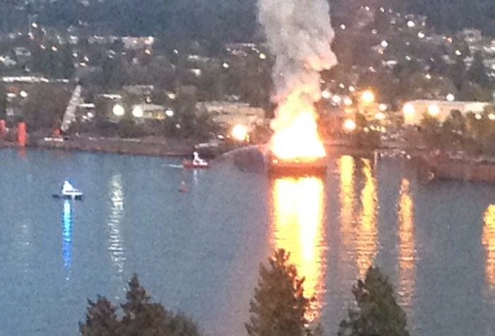 A fire boat can be seen pouring water on the burning barge. - MATT LORENZI