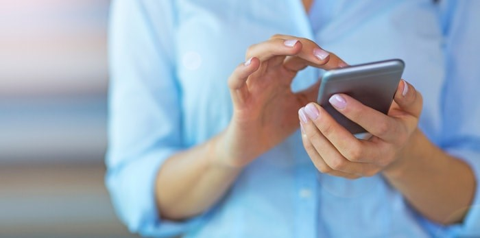 Get ready: Cellphones across B.C. will buzz on Wednesday, November 27 as the province tests our wireless emergency alert system. Photo: Woman using smartphone/Shutterstock