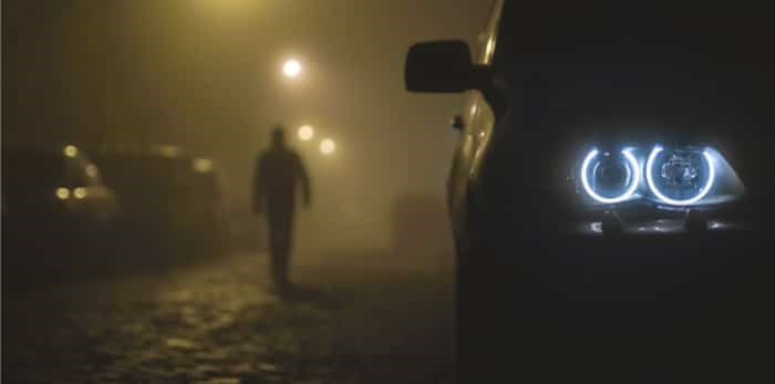 Photo: car headlight with a walking man on a fog background / Shutterstock