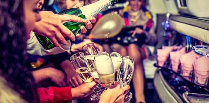 Drinking champagne in a limo/ Shutterstock