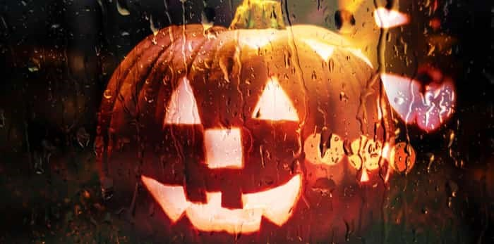 Photo: scary halloween pumpkins behind a window in the rain / Shutterstock
