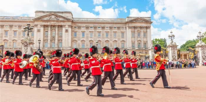Photo: LONDON, UNITED KINGDOM - JULY 11, 2012: The band of the Coldstream Guards marches in front of Buckingham Palace during the Changing of the Guard ceremony. / Shutterstock