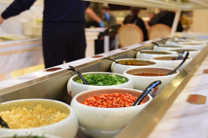 Customers choose their own sauces for their meals at a topping bar. Photo: Megan Devlin