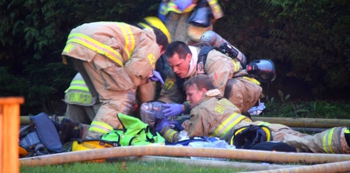 Burnaby firefighters perform CPR on the victim of a house fire. Photo by Curtis Kreklau