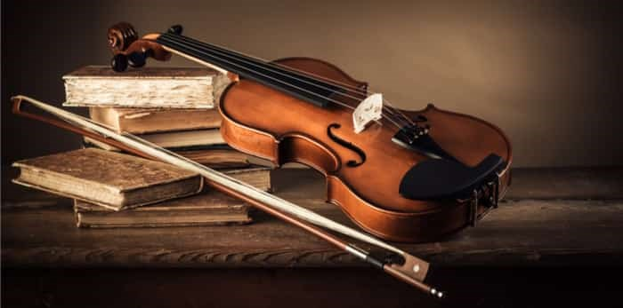 Photo: Violin, bow and old books on a rustic wooden table, arts and music concept / Shutterstock